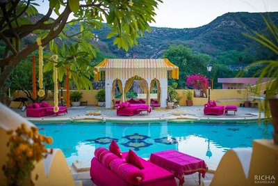 Samode Palace, Jaipur decorated and dolled up in hues of fuchsia and Marigold flowers for an outdoor mehendi ceremony