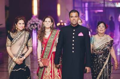 Black achkan suit with gold button details and pink pocket square