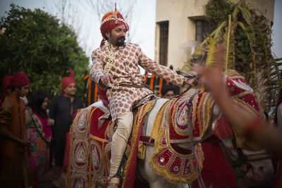 Groom riding to the wedding venue on a decorated white horse