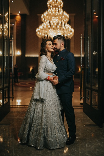 The bride flaunts a silver sizzling lehenga, while the groom looks dapper in a navy blue bandhgala.