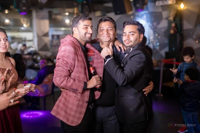 The groom posing with his father and brother