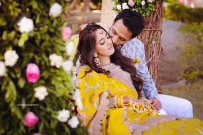 Bride and groom posing romantically at their mehendi