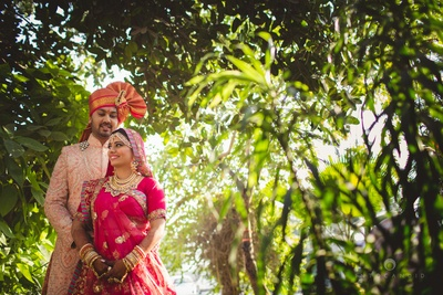 Couple dressed in complementing rose gold and pink wedding outfits for an outdoor wedding ceremony held at I-Lawns, Wadala