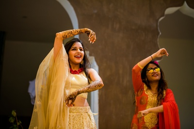 a candid capture of the bride and her bridesmaid dancing at the mehendi ceremony