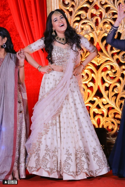 White and pastel pink lehenga with silver embroidery styled with minimal makeup and jewellery for sangeet look.