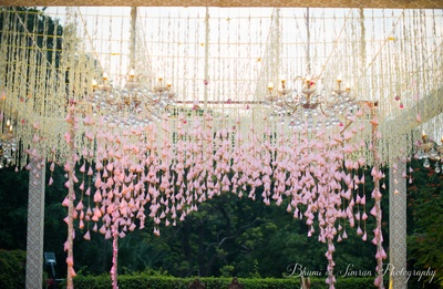 Gorgeous wedding decor with chandeliers and pink tassels.