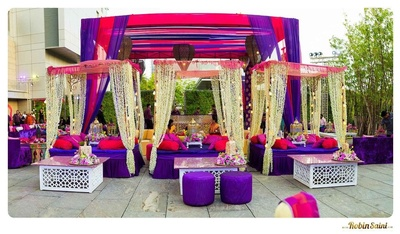 Wedding venue decorated with raani pink and purple drapes, cabanas, bolsters, and Mogras