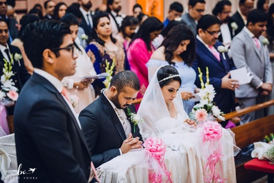 The bride and groom seated in prayer during the wedding ceremony.