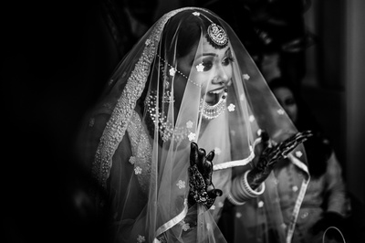 a candid black and white picture of the bride under a veil