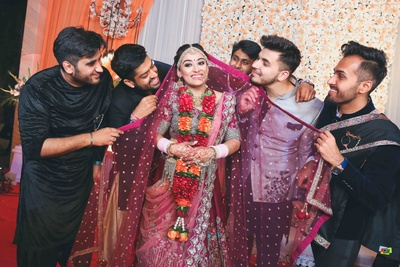 Bride in red lehenga poses with her brothers, all in matching colors