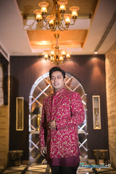 Red and maroon bandhgala embellished with zari work for the sangeet ceremony