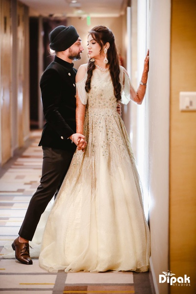Manjot dressed in a beautiful ivory gown with cold shoulders and hand embroidery for the engagement ceremony