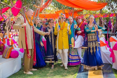 Wedding guests dressed in royal indian outfits enjoying and dancing to desi wedding beats