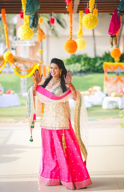 Off-white embroidered short kurta and pink palazzo pants with sheer embellished dupatta for the mehendi ceremony