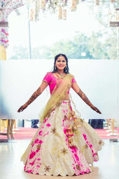 The bride looks gorgeous in this raani pink and white lehenga with a sheer ochre dupatta