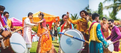 Bride dances away happily in a warm colour palette of yellow and pink hues while the the groom compliments her in a cream ensemble.