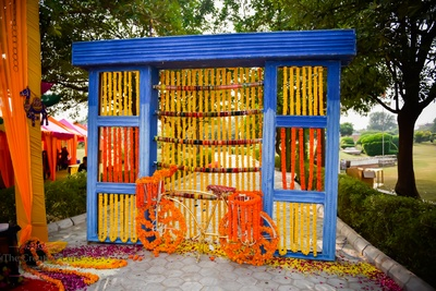 Wooden installation painted in blue and adorned with Marigold strings and glass bangles