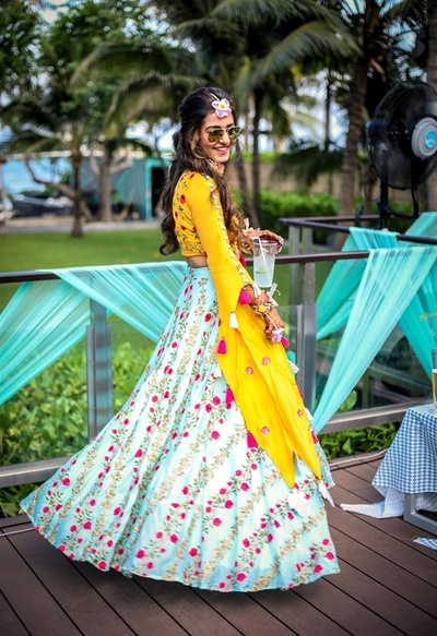 The bride twirling in her pastel blue and yellow lehenga at the pool party