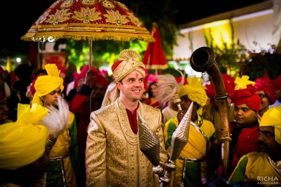 Groom entering dressed in a gold sherwani with royal Indian band baaja at Samode Palace, Jaipur