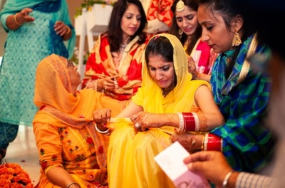 The bride gets emotional during her haldi ceremony with her family members.