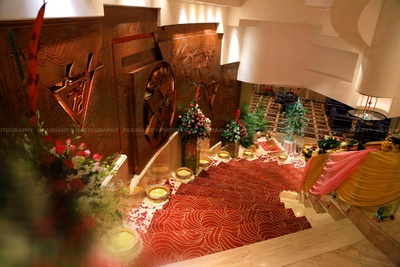 Stairways decorated with clustered floral arrangement, brass pots surrounded with Rose petals, and floral strings