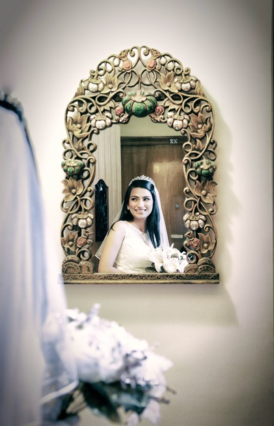 Fresh flower bridal bouquet of white lilies reflected in an antique, whimsical carved and painted wooden mirror
