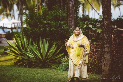 Mother of the bride dressed in an ivory suit embellished with applique and gold heirloom jewellery