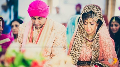 Stunning groom's attire in blush hues with a fuchsia turban at the Gurudwara wedding ceremony