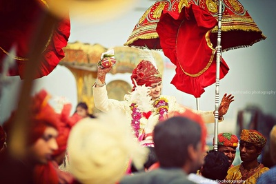 Traditional entry of the groom on a horse with a traditional red decorative umbrella
