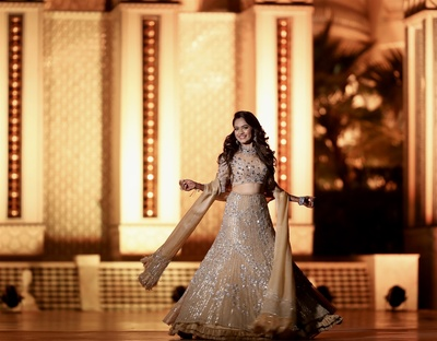 The bride twirling in a golden heavily embellished lehenga at the sangeet