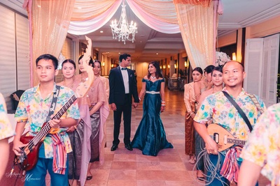 Bride and groom enter their reception in complimentary outfits