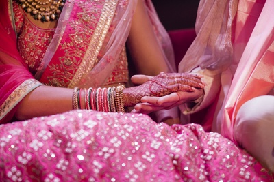 A close-up shot of the bride and groom holding hands during their wedding rituals.