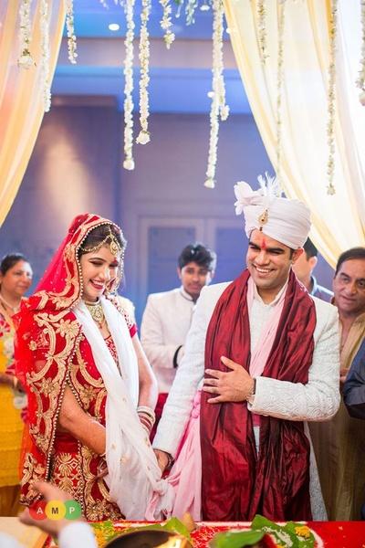 Textured white sherwani styled with a maroon silk odhni