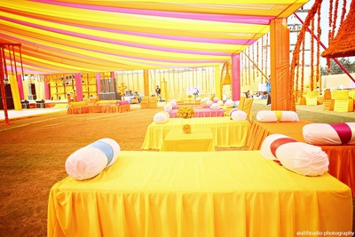 Bolsters and yellow coordinated decor for mehendi ceremony