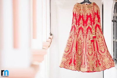 Red wedding lehenga embellished with floral patches of embroidery, stones, zari work and pom poms