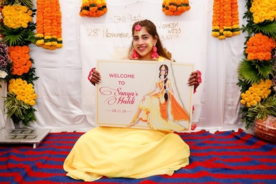 The bride hold up a cute signage during her haldi ceremony.