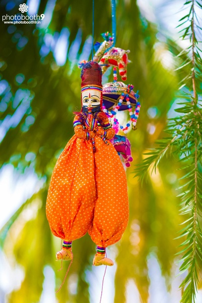 Outdoor wedding venue decorated with suspended Rajasthani dolls