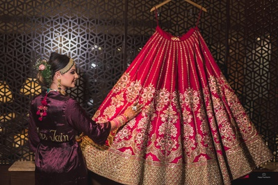 The bride stands admiring her gorgeous dark pink sabyasachi lehenga!