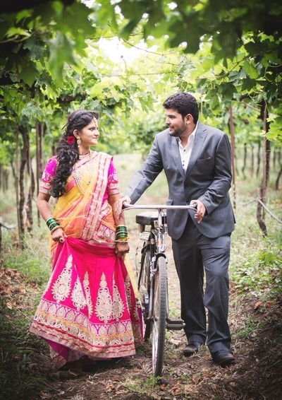 Dressed in lehenga choli and metal grey suit, couple posing along with a cycle to add an ethnic touch