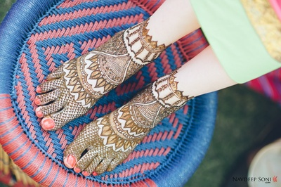 Bridal feet covered in intricately covered in indian mehndi design for feet