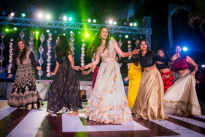 a candid capture of the bride and her bridesmaids dancing at the sangeet ceremony