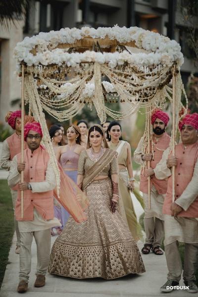 The bride walking towards the wedding venue under a phoolon ki chaadar.