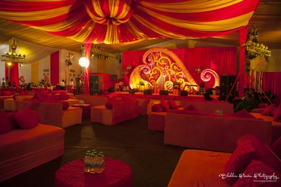 Indoor Mughal style setting with stage decorated with artistic designs and real flowers