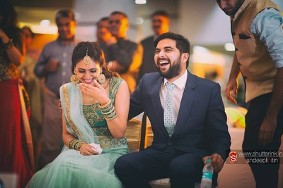 Groom clothed in a well cut navy suit styled with a aqua neck tie embellished with polka dots