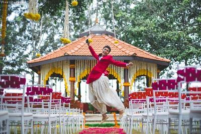 Groom dancing in joy in front of the wedding mandap.