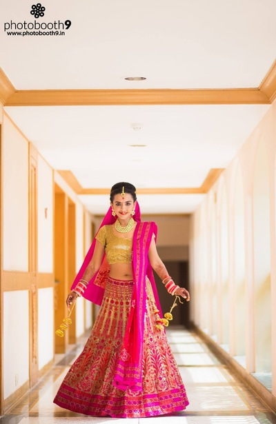 Pink wedding lehenga embellished with embroidered motifs, styled with gold sequined choli and minimal polki studded jewellery