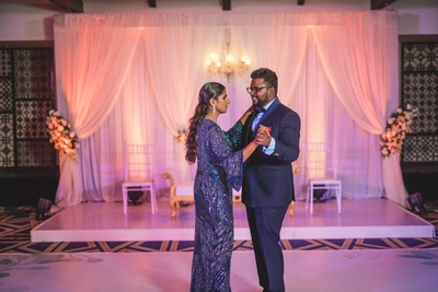 The couple dancing at their reception, flaunting perfectly coordinated blue outfits.