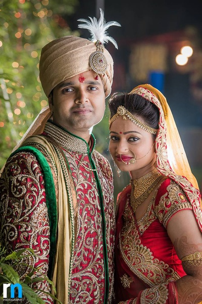 Red wedding sherwani with gold dupatta and a matching feather topped Safa