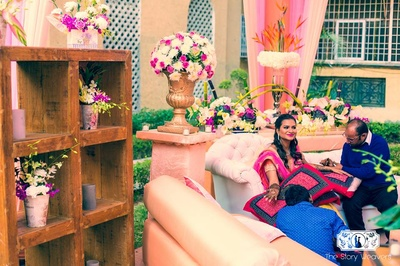 Outdoor mehndi ceremony set up in hues of pink and peach with fresh flowers, drapes and wooden shelves