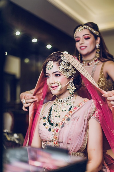 bride getting ready in statement wedding jewellery and pastel lehenga